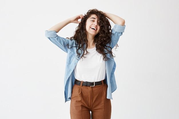 Modelo feminino emocional bonito, vestindo longos cabelos ondulados soltos tem um sorriso largo agradável e encantador, sonha com férias com o namorado. felicidade e alegria