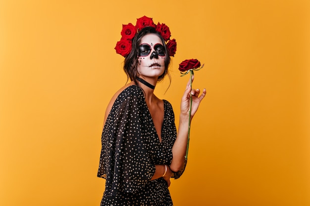 Modelo feminino encantador em um vestido elegante, apreciando o perfume de rosas. retrato de menina com maquiagem de halloween, posando em quarto laranja.