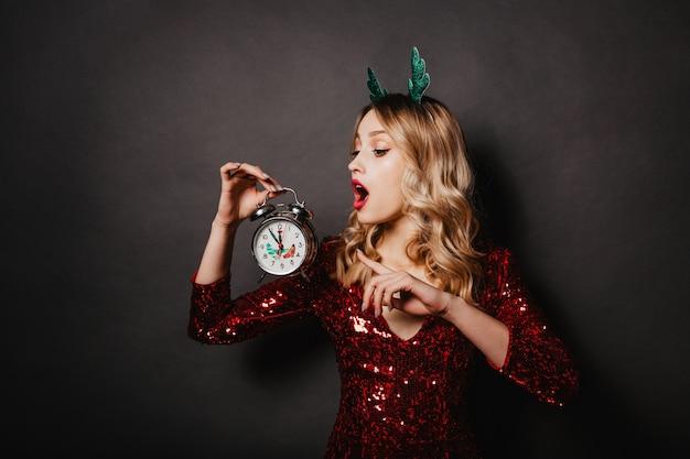 Modelo feminino encaracolado chocado posando na parede com relógio
