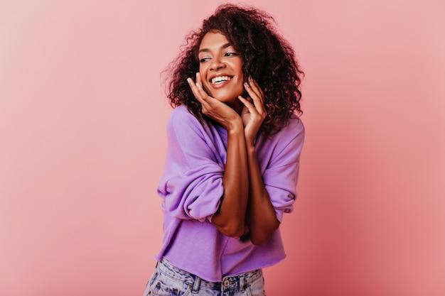 Modelo feminino entusiasmado posando em rosado com felicidade sincera. retrato interior de uma garota africana elegante.