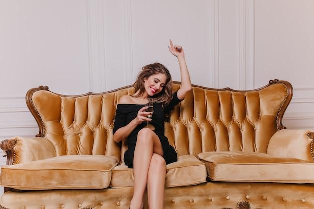 Modelo feminino espetacular no elegante vestido preto, aproveitando a festa, sentado no sofá e rindo. jovem bem vestida com taça de champanhe relaxante no evento.