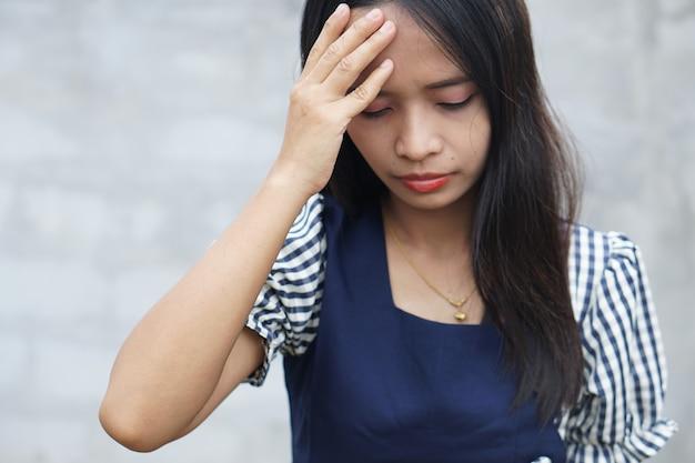 Modelo feminino estressante e sobrecarregado de fadiga mantém as mãos nas têmporas Foto Premium