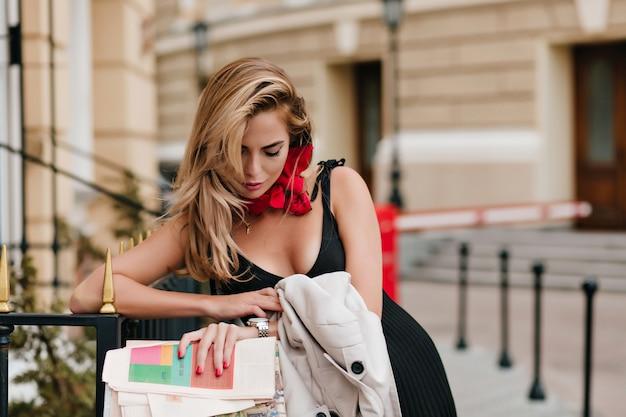 Modelo feminino europeu cansado olhando para o relógio de pulso enquanto espera alguém no beco em um lindo traje