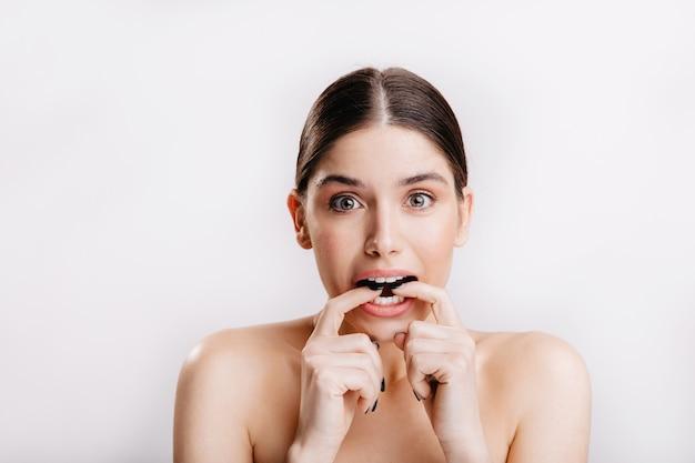 Modelo feminino europeu com pele saudável morde os dedos de medo, posando na parede isolada.