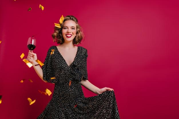 Modelo feminino feliz com cabelo encaracolado brilhante posando com um copo de vinho no fundo clarete