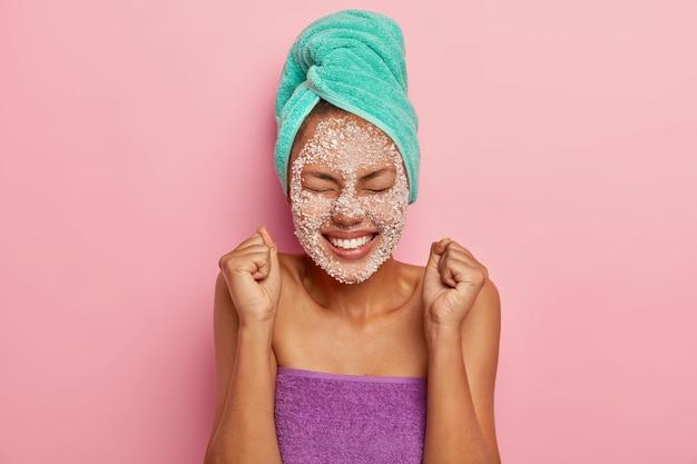 Modelo feminino feliz e energizado ergue os punhos cerrados, regozija-se com o momento agradável da vida, de olhos fechados, sorriso dentuço, aplica máscara srcub de sal marinho na pele para reduzir as linhas de expressão
