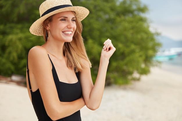 Modelo feminino feliz satisfeito posa de biquíni preto e chapéu de palha, tem um largo sorriso enquanto olha para o sol, fica na praia perto do mar ou oceano, sorri com alegria. pessoas, horário de verão e conceito de descanso