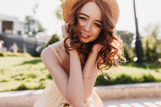 Modelo feminino glamoroso com cabelo ruivo, posando com um sorriso fofo na natureza. foto ao ar livre de menina bem-humorada com chapéu de palha, apreciando a sessão de fotos no parque.