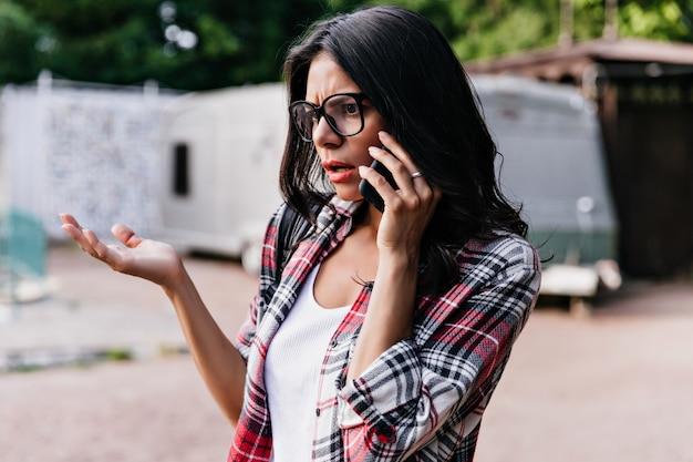 Modelo feminino infeliz com cabelo castanho, falando no telefone e acenando com a mão. retrato ao ar livre da maravilhosa garota latina posando durante uma conversa.