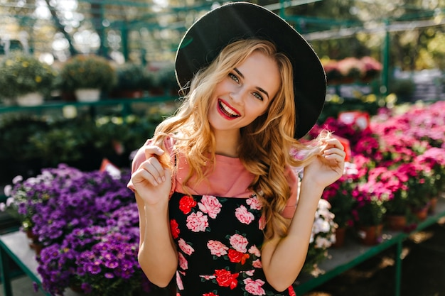 Modelo feminino inspirado em pé de chapéu em frint de flores coloridas. retrato de uma mulher atraente cega relaxante na laranjeira.
