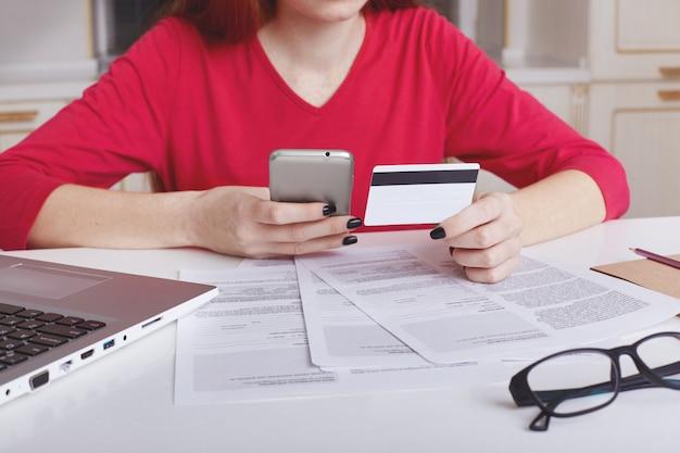 Modelo feminino irreconhecível na camisola vermelha senta-se na mesa de trabalho, rodeada de papéis e computador portátil