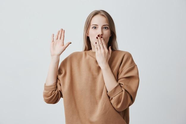 Modelo feminino jovem chocado com cabelos loiros tingidos lisos sendo confundido, posando contra uma parede cinza com olhos esbugalhados, escondendo a boca atrás da mão