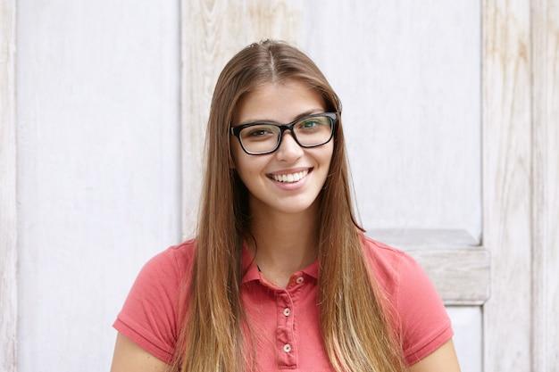 Modelo feminino jovem e atraente usando óculos retangulares posando dentro de casa contra uma parede de madeira