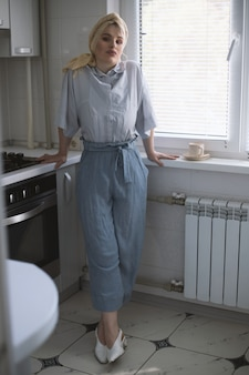 Modelo feminino loiro atraente na cozinha, desfrutando de uma xícara de chá