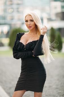 Modelo feminino loiro elegante de vestido preto, posando para a câmera em pé ao ar livre. estilo e conceito de moda
