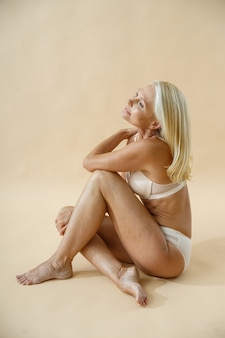 Modelo feminino loiro maduro posando de cueca, sentado no chão do estúdio e olhando para longe, isolado