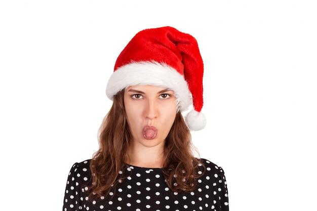 Modelo feminino morena insatisfeito tem expressão nojenta, mostra a língua, irritada com alguém, garota emocional no chapéu de natal papai noel isolado no branco