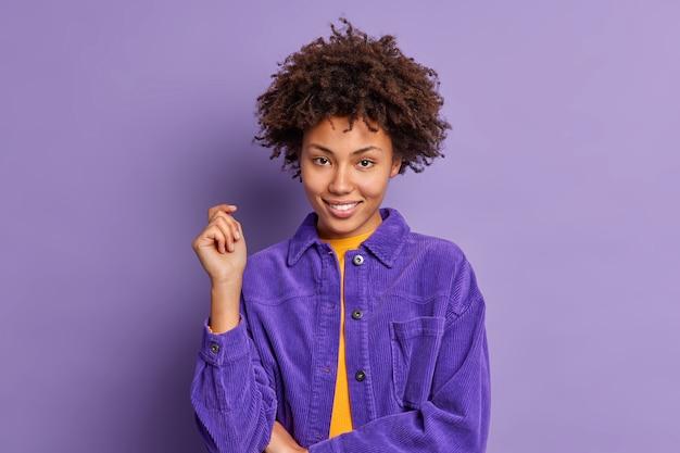 Modelo feminino muito autoconfiante com cabelo afro mantém a mão levantada sorri suavemente olha diretamente ouve atentamente interlocutor veste jaqueta de veludo estilosa.