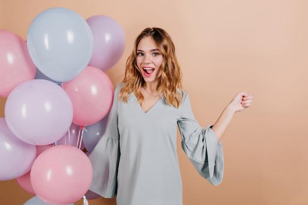 Modelo feminino muito europeu em roupa azul, posando com um sorriso surpreso ao lado de balões