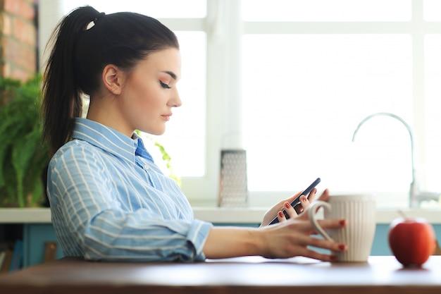 Modelo feminino na camisa azul, brincando com o telefone dela e tomar um copo de bebida