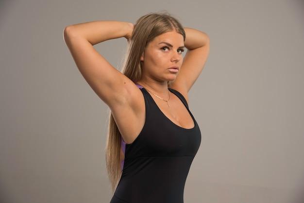 Modelo feminino no sutiã esporte coloca as mãos atrás da cabeça.