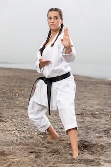 Modelo feminino no treinamento de traje de karatê