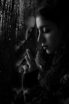 Modelo feminino perto de janela com gotas de chuva