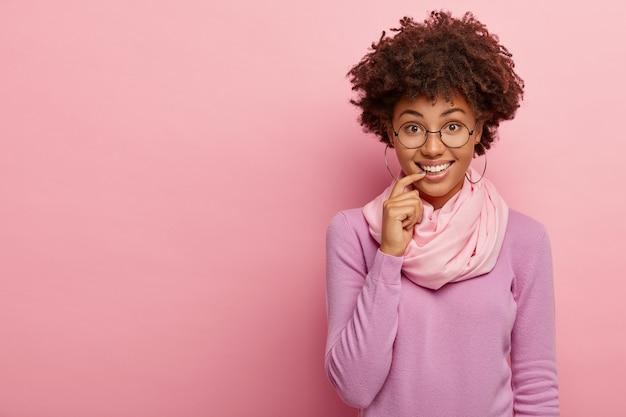 Modelo feminino positivo de pele escura com sorriso encantador, mantém o dedo indicador nos lábios, olha através dos óculos, usa modelos casuais de macacão dentro de casa, tem expressão facial relaxada
