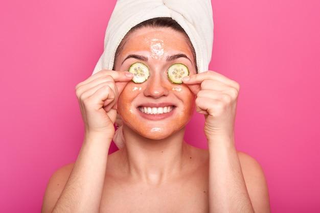 Modelo feminino positivo mima a pele, aplica máscara de beleza no rosto