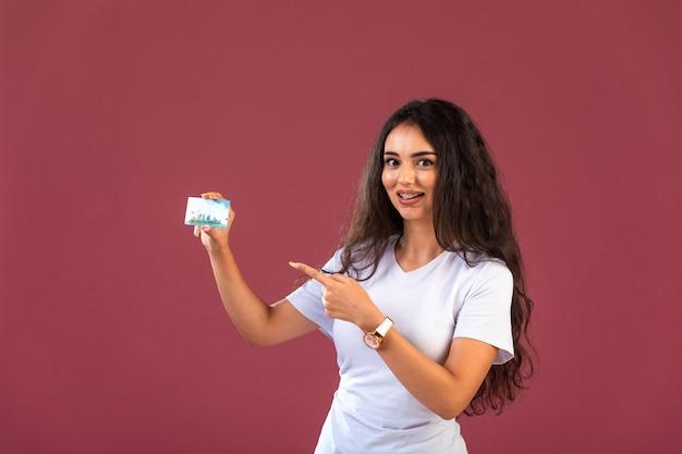 Modelo feminino promovendo novo produto bancário e apontando para ele