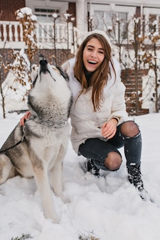 Modelo feminino refinado em roupas quentes, brincando com o cão husky durante as férias de inverno. retrato ao ar livre de uma jovem deslumbrante brinca com o animal de estimação na manhã de dezembro.