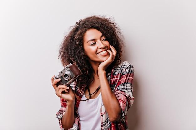 Modelo feminino relaxado com a câmera, passando o tempo. linda garota negra curtindo seu hobby.