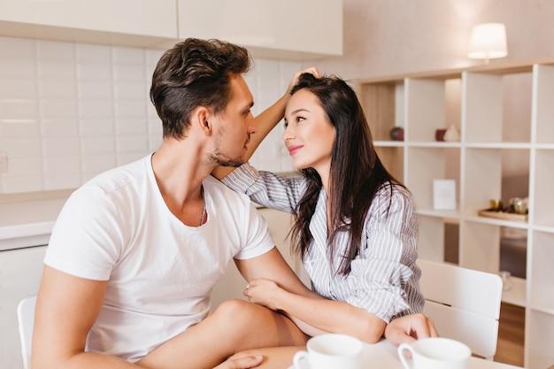 Modelo feminino romântico com cabelo liso olhando para o marido com ternura após o café da manhã