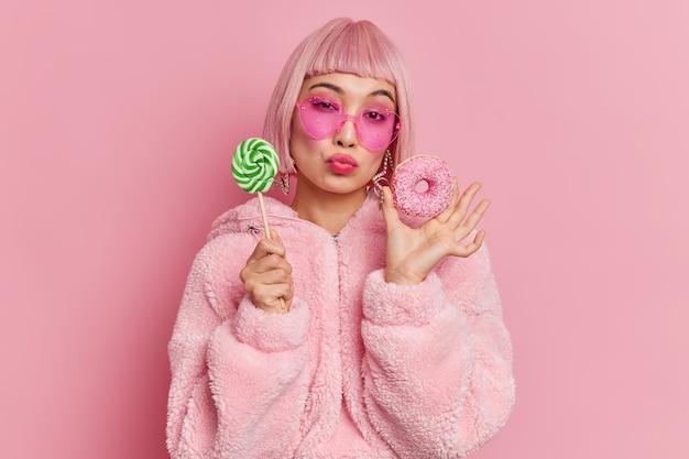 Modelo feminino romântico na moda com cabelo rosa e glamour tem um dente doce, segurando um pirulito e um donut coberto com um casaco de pele quente, óculos de sol da moda