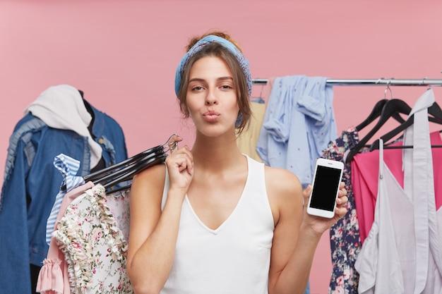 Modelo feminino satisfeito, pressionando os lábios, de pé contra manequin e rack com roupas, segurando hagers com vestuário e telefone celular com tela em branco, tendo bom humor após compras bem-sucedidas