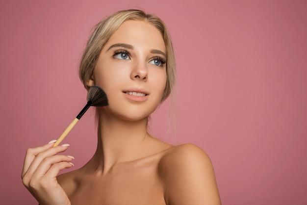 Modelo feminino segurando maquiagem escova