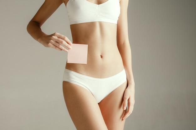 Modelo feminino segurando um cartão vazio perto do estômago