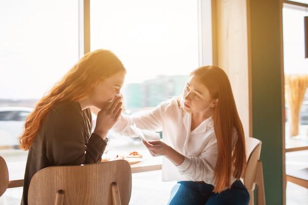 Modelo feminino senta-se em um café com a amiga e assoa o nariz. jovem mulher está doente.