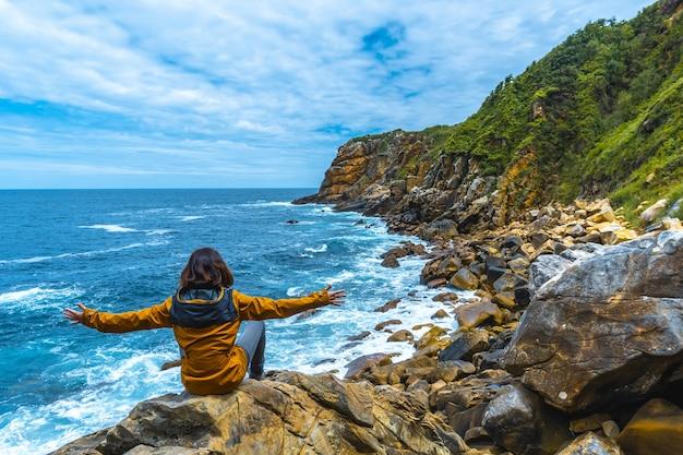 Modelo feminino sentado na praia olhando com satisfação para o lindo mar