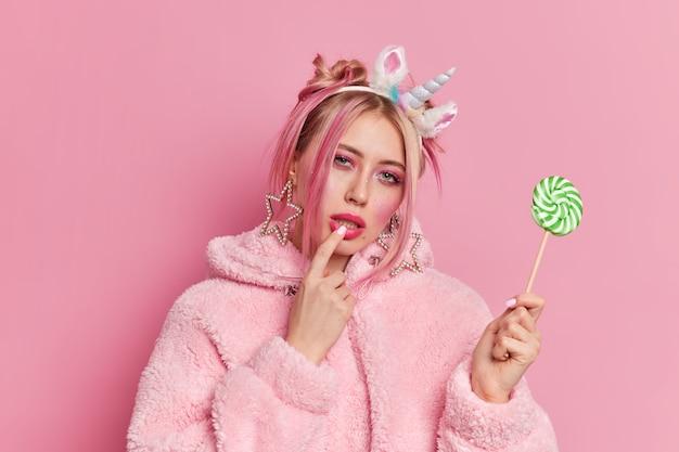 Modelo feminino sério com maquiagem brilhante mantém o dedo nos lábios e olha misteriosamente para a câmera segurando um pirulito verde