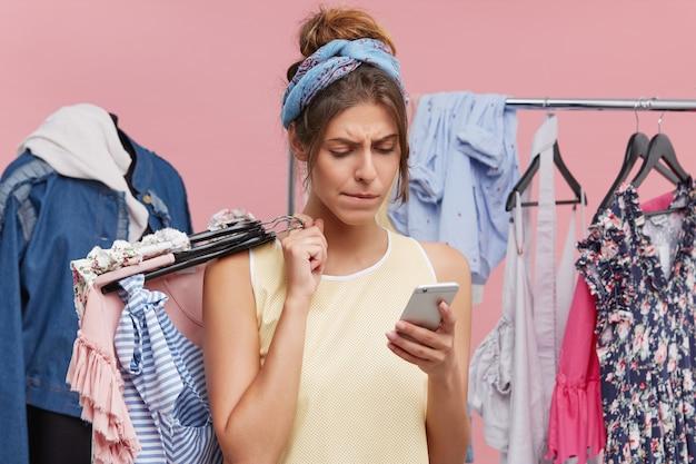 Modelo feminino sério de pé contra a figura leiga e a prateleira de roupas, segurando os cabides com roupas em uma mão e o telefone inteligente lendo sobre descontos na loja de roupas.