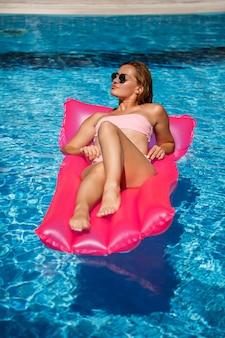 Modelo feminino sexy, descansando e tomando banho de sol em um colchão na piscina. mulher em um maiô de biquíni rosa flutuando sobre um colchão inflável rosa. fps e protetor solar