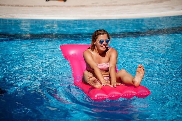 Modelo feminino sexy em óculos de sol, descansando e tomando banho de sol em um colchão na piscina. mulher em um maiô de biquíni rosa flutuando sobre um colchão inflável rosa. fps e protetor solar