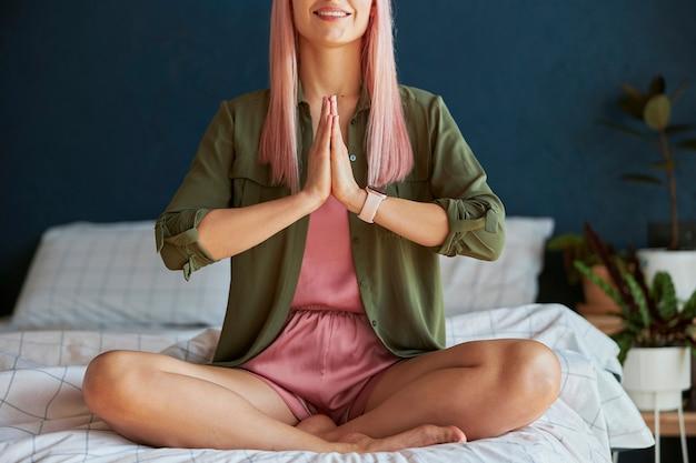 Modelo feminino sorridente medita de mãos dadas em namaste mudra na cama grande closeup