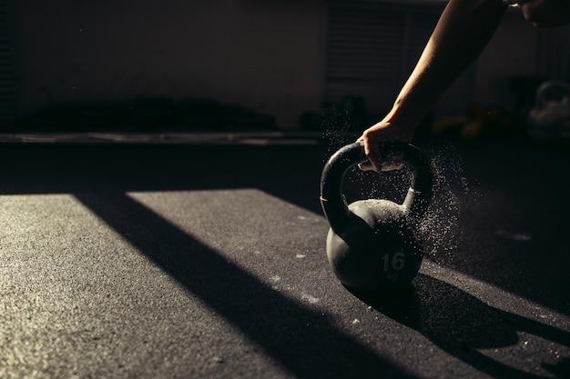 Modelo feminino tomar chaleira com talco em uma academia antes de fazer excersis.