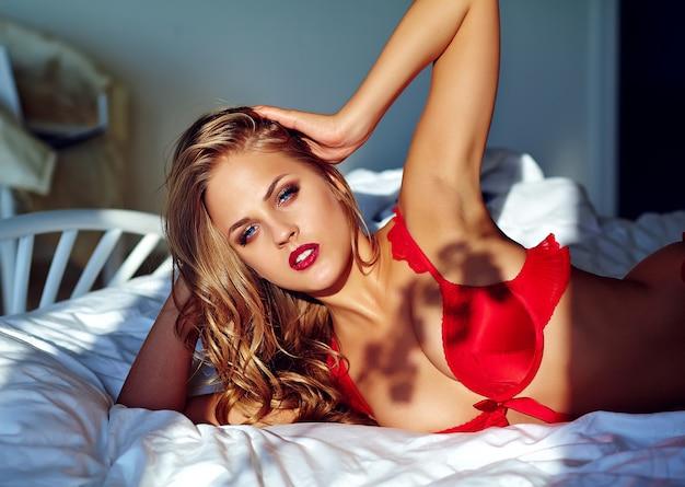 Modelo feminino vestindo lingerie erótica vermelha na cama de manhã