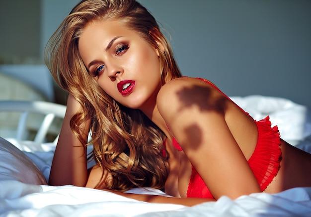 Modelo feminino vestindo lingerie vermelha na cama de manhã