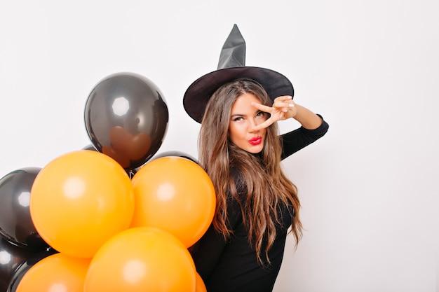 Modelo fofo curtindo a sessão de fotos de halloween na parede branca