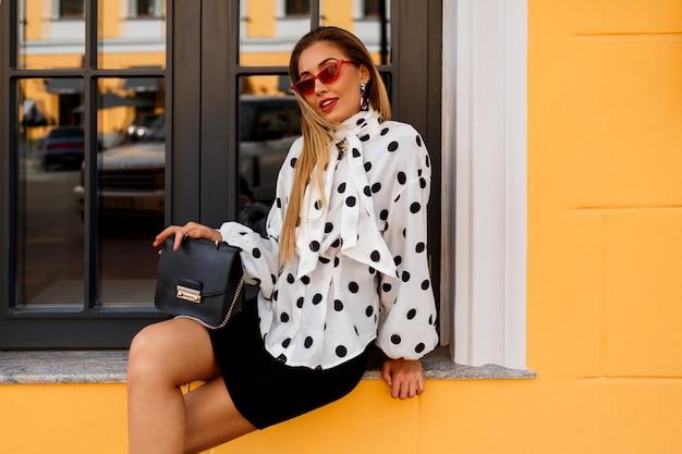 Modelo gracioso demonstrar estilo de moda primavera elegante. segurando bolsa de luxo