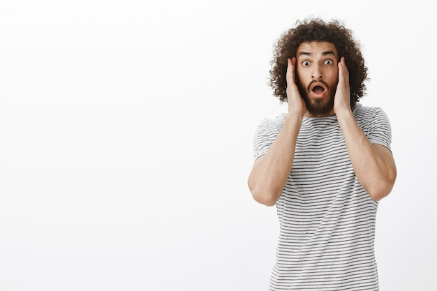 Modelo hispânico surpreso e atordoado com barba e cabelo encaracolado, segurando as palmas das mãos nas bochechas e deixando cair o queixo de espanto e medo